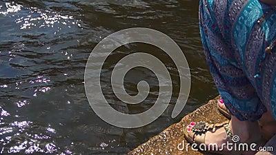 Frau, die auf Damm sitzt und schönes Sommerwetter genießt stock video