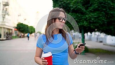 Frau, die auf dem Smartphone und dem trinkenden Kaffee gehen hinunter die Straße spricht Langsame Bewegung stock video