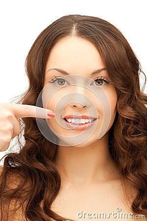 Frau, die auf ihr toothy Lächeln zeigt