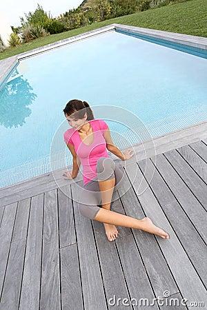 Frau, die auf Poolplattform sitzt