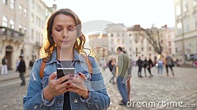 Frau, die bei Sonnenuntergang mit dem Smartphone eine alte Straße entlang geht Kommunikation, soziale Netzwerke, Konzept des Onli stock video footage