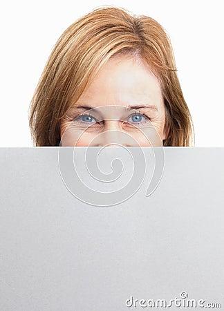 Frau, die ihr Gesicht hinter leerem Blatt versteckt