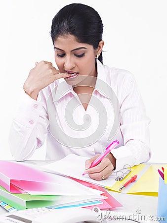 Frau, die an ihrem Büroschreibtisch arbeitet