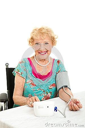 Frau, die ihren eigenen Blutdruck nimmt