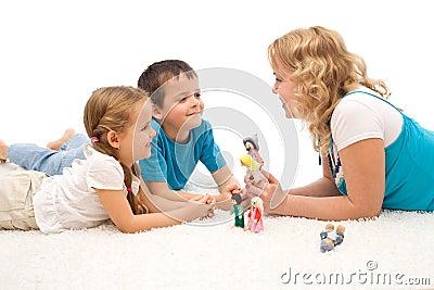 Frau, die ihren Kindern auf dem Fußboden eine Geschichte erklärt