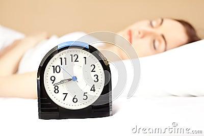 Frau, die im Bett (Fokus, schläft auf Alarmuhr)