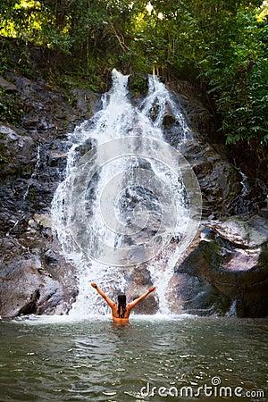 Frau, die im schönen Wasserfall sich erneuert