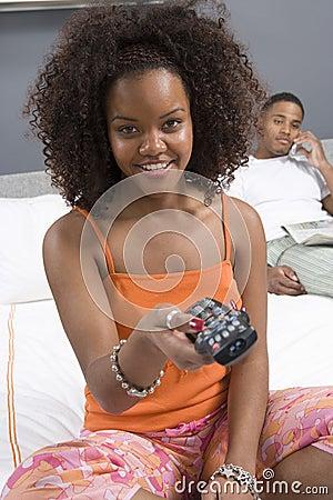 Frau, die im Schlafzimmer fernsieht