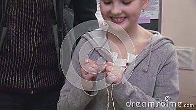Frau, die kleinem Mädchen mit Blume auf dem Kopf strickt durch Häkelarbeit hilft festival kreation handmade stock video