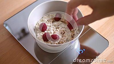 Frau, die Lächeln-Gesicht mit Himbeeren in der Hafermehl-Schüssel auf Lebensmittel-Skala macht Gesundes Frühstück für Kinder 4K stock footage