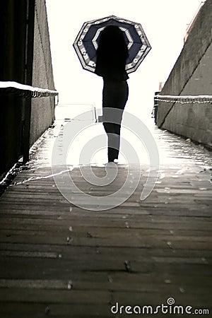 Frau, die mit Regenschirm geht