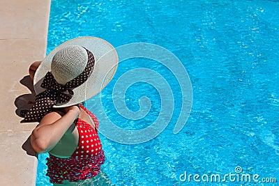 Frau, die am Pool sich entspannt