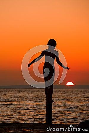 Frau, die am Sonnenaufgang meditiert