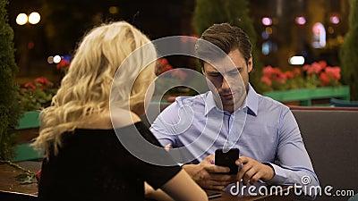 Frau, die versucht, Aufmerksamkeit ihres Freundes zu erregen die aktiv arbeitend an Telefon stock video