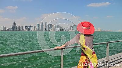 Frau durch Meerblick und Stadtbild von Doha stock video footage