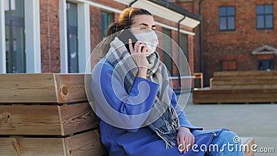 Frau in Gesichtsmaske, die Smartphone in der Stadt anruft stock footage
