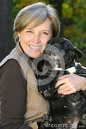 Frau hält einen Hund an