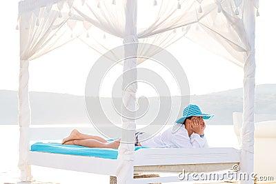 Frau im Hut, der auf Bett in dem Meer sich entspannt