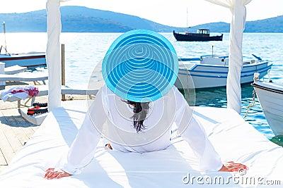 Frau im Hut, der auf weißem Luxusbett sich entspannt