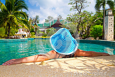 Frau im Hut, der in der tropischen Rücksortierung sich entspannt