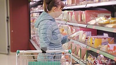 Frau im Supermarkt Junge kaukasische Frau im Matroseleseaufkleber des Käses es in den Wagen einsetzend stock footage