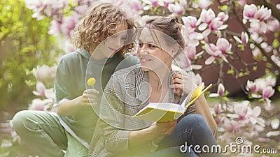 Frau liest ein Buch auf einem HinterBusch, der rosa Magnolia blüht Ein kurviger Sohn kommt auf sie zu und gibt einen Löwenzahn stock footage