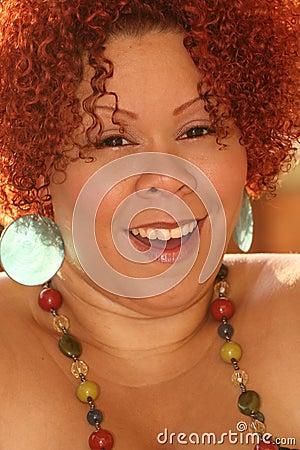 Frau mit dem lockigen roten Haar und den hellen Schmucksachen