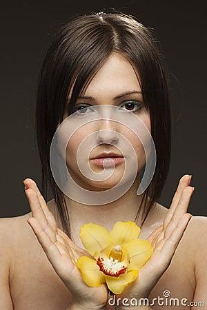 Frau mit Orchidee in ihren Händen