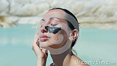 Frau mit schwarzem Clay Facial Mask Schönheit, Wellness Badekurort im Freien stock footage