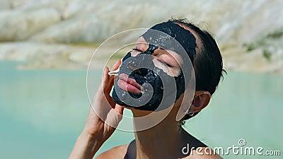 Frau mit schwarzem Clay Facial Mask Schönheit, Wellness Badekurort im Freien stock video footage