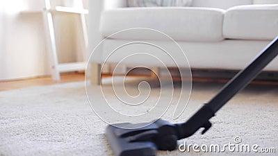 Frau mit Staubsauger-Reinigungsteppich zu Hause