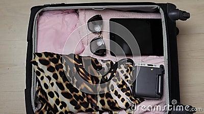Frau ` s offene Tasche auf einem Desktop mit Kleidung und Zubehör, ist sie verpackend und fertig zu gehen, zu reisen werden und stock footage