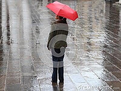 Frau unter rotem Regenschirm