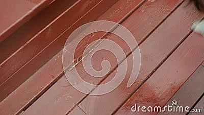 Frauen in Handschuhen, die braun-braune Holzfarbe im Freien waschen Die Hausfrau, die im Sommer auf der Holzbank putzt, hat eine  stock video