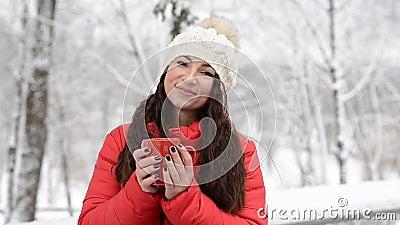 Frauen trinken heißes Tee oder Kaffee aus dem Cup im gemütlichen Schneehaus Garten am Wintermorgen Schönes Mädchen im Winter mit stock video
