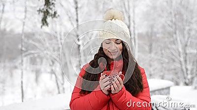 Frauen trinken heißes Tee oder Kaffee aus dem Cup im gemütlichen Schneehaus Garten am Wintermorgen Schönes Mädchen im Winter mit stock video footage