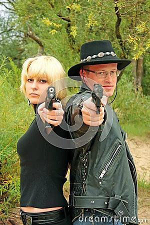 Frauen und zielende Wechselpistolen des Mannes