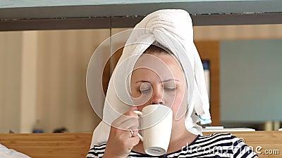 Frauen in weißem Handtuch trinken Kaffee oder Tee im Bett im Hotelzimmer oder im Wohnzimmer stock video footage