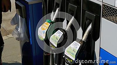 Frauenhand unter Verwendung der Zapfpistolen an einer Tankstelle Tankstelle Füllen des Autos mit Kraftstoff stock footage