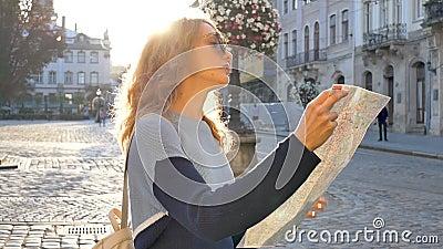 Frauenporträt einer Touristinnen mit Sonnenbrille und Papierkarte in ihren Händen auf der Suche nach einer Richtung früh in der stock video