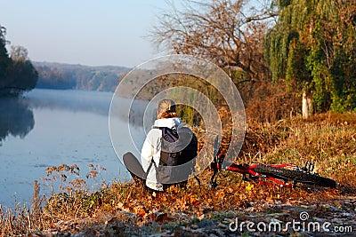 Frauenradfahrererholung auf dem Flussufer