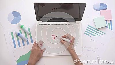 Frauenschreiben JOB auf einem Blatt Papier auf Laptop Geschäftsdesktop mit Diagrammen stock footage