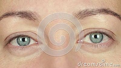 Frauenwachsame augen und vordere Kamera Blinkens Schließen Sie herauf die erwachsene Frau des Gesichtes, die Auge blinzelt stock footage
