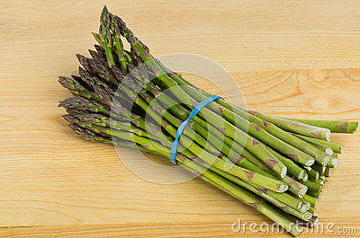 Freash asparagus on wooden cutting board