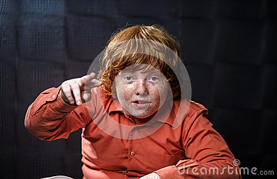 Freckled red-hair boy posing on dark background.