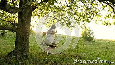 Free girl swinging on a swing on an oak branch in sun. Dreams of flying. Happy childhood concept. Beautiful girl in a. Free girl swinging on swing on an oak stock video footage
