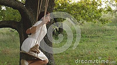 Free girl swinging on a swing on an oak branch in sun. Dreams of flying. Happy childhood concept. Beautiful girl in a. Free girl swinging on swing on an oak stock video