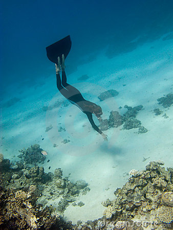Freediver girl dives toward sea bottom