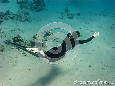 The freediver girl swims along sand sea bottom