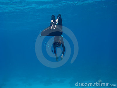 Freediver with monofin makes turn near sea bottom